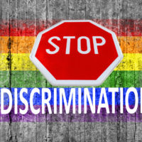 STOP sign and discrimination on top of LGBT flag painted on background