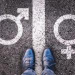 male and female gender symbols on asphalt below legs