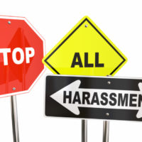 Three signs that read stop all harassment