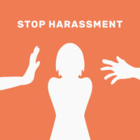 orange sign that reads stop harassment