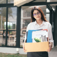 business woman fired walks out with stuff in box