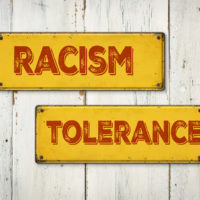 Racism and tolerance Direction signs on a wooden wall