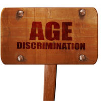 wooden sign that reads age discrimination