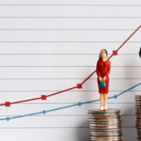 Miniature people toys standing on a pile of coins in front of a graph