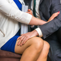 Male worker touches woman's knee while woman resists
