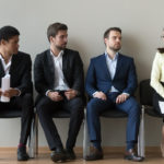 Diverse male applicants looking at female rival waiting for interview