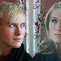 man looks in reflection sees female version of self
