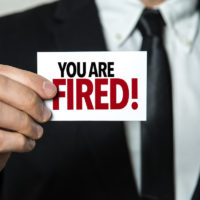 You Are Fired written on notecard held by businessman