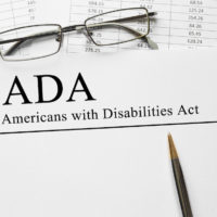 Notepad that reads Americans with Disabilities Act (ADA) on a table with spectacles and pen