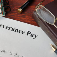 Severance Pay doc, glasses, planner and pen on table