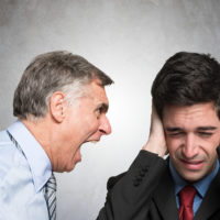 Angry businessman shouting at employee