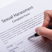 Human Hand Filling out Sexual Harassment Complaint Form