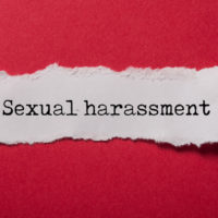 closeup of white torn paper on red paper background with text Sexual harassment