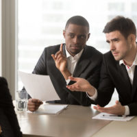male recruiter doubting gestures toward female interviewee