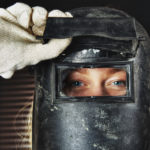female welder wearing helmet