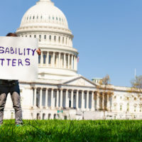 Protester boy holding sign disability matters hiding face