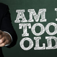 Business man pointing with the text: Am I Too Old?