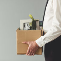 Businessman getting fired holding a box with stuff
