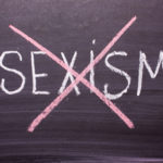 Stop sexism is written on a chalkboard crossed out