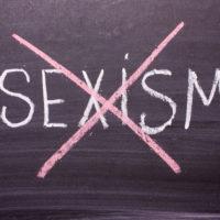 Stop sexism is written on a chalkboard crossed out