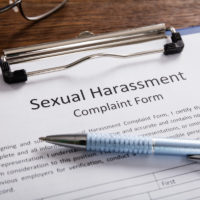 Sexual Harassment Complaint Form With Pen and glasses on desk