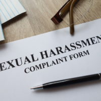 Sexual harassment complaint form with pen, calculator and glasses on desk