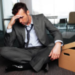 Sad fired businessman sitting with box outside meeting room