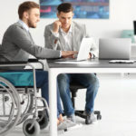 disabled businessman in wheelchair with coworker on laptops