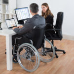 Disabled employee in wheelchair, talking with boss