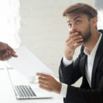 Shocked worker getting dismissal notice from boss