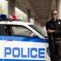 handsome african american police officer with crossed arms leaning back on car and looking at camera
