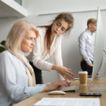 older woman being talked to by boss