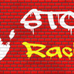 stop racism graffiti written over bricks and handprint