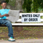 A non-white man sits on a bench in a park reserved for whites