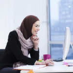 Beautiful Arabic business woman working on computer. Woman in her office