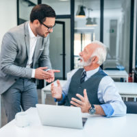 Young man encouraging older worker to retire