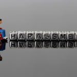 Miniature scale model man in a wheelchair with the word harassment on beads reflected on a dark background