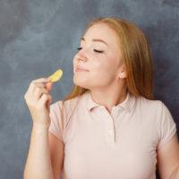 Cute young woman enjoy eating potato chips