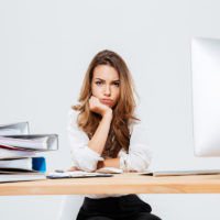 Upset sad businesswoman sitting at her working place
