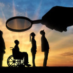Employer's hand looks through the magnifying glass to an invalid in a wheelchair waiting for an interview for work