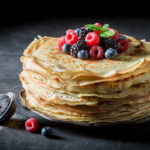 Big stack of pancakes with blueberries and raspberries