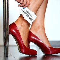 "Sexual harassment alert with young woman with red high heels shoes showing a note with the text ""sexual harassment"""