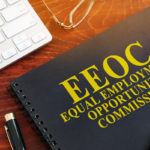 Book that reads eeoc on desk with pen and keyboard