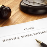 hostile work environment claim form next to pen and gavel on table