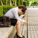 depressed business woman sitting on the bench after being fired