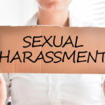 sexual harassment text on cardboard sign