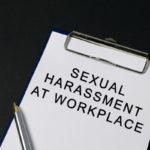 Sexual harassment at workplace word on paper - black background