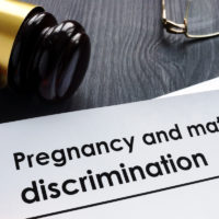 Documents about pregnancy and maternity discrimination and gavel.