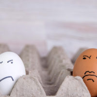 prejudices of racism: two eggs of different colors with dislike look at each other, short focus