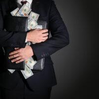 Businessman holding briefcase with dollar banknotes on dark background. Corruption concept